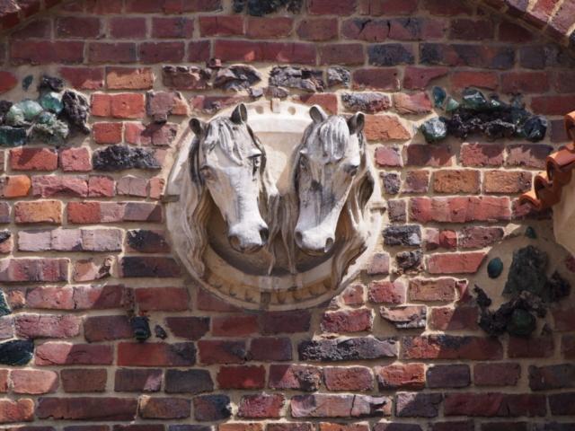 Rzeźba dwóch końskich głów na tle ceglanej ściany